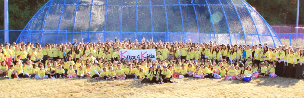 Over 200 campers and staff from the kars4Kids summer camp TheZone holding a Kars4Kids banner