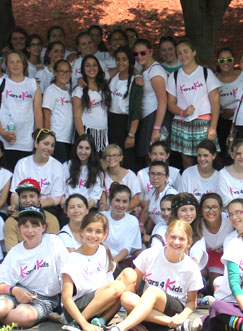 A very large group of girls wearing Kars4Kids teeshirts pose for a picture