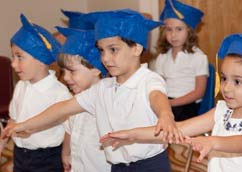 Children wearing graduation caps in a Kars4Kids sponsored preeschool