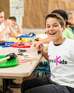 A young boy smiling as he does an arts and crafts project