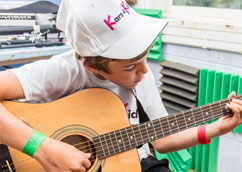 Young boy learning how to play the guitar