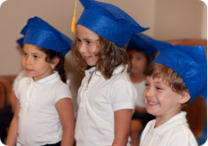 Children wearing graduation caps in a Kars4Kids sponsored preschool