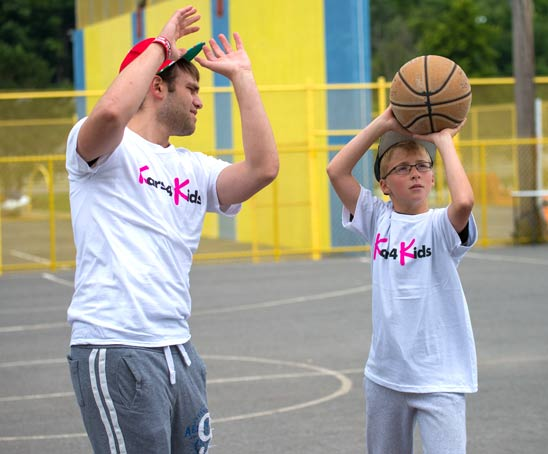 A teenage mentor teaching a young boy how to shoot a basketball during summer camp